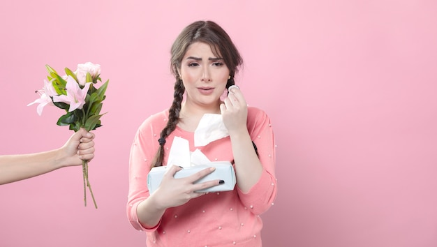 Front view of crying woman being offered bouquet of lilies while holding napkins Free Photo