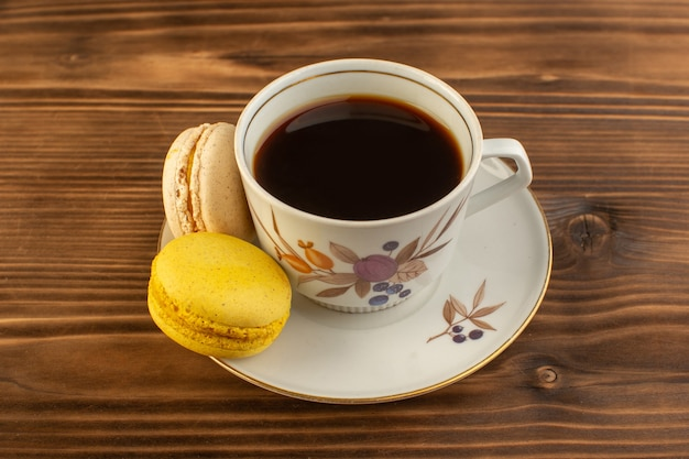 A front view cup of coffee hot and strong with french macarons on the brown wooden rustic desk coffee hot drink Free Photo