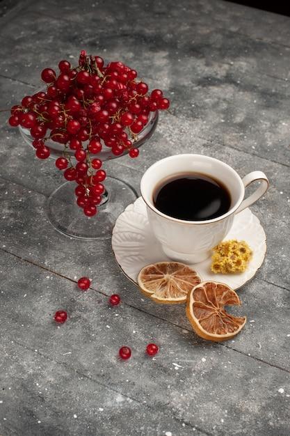 灰色のデスクコーヒーベリーフルーツに新鮮な赤いクランベリーとコーヒーの正面図カップ 無料写真