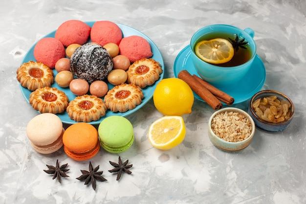 フレンチマカロンクッキーと白い表面のケーキとお茶の正面図ビスケットクッキー甘いケーキキャンディークッキー 無料写真