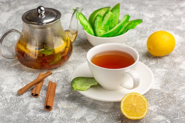 ライトホワイトの表面にレモンとシナモンが入った正面図のお茶 無料写真