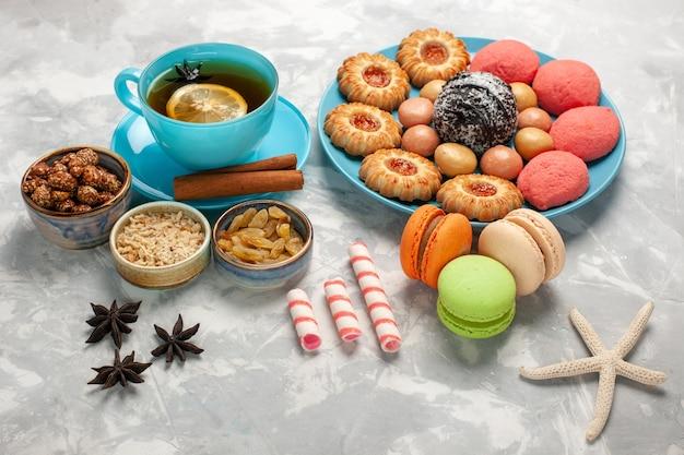 マカロンクッキーと白い表面のケーキとお茶の正面図ビスケットクッキーシュガースイートケーキキャンディー 無料写真