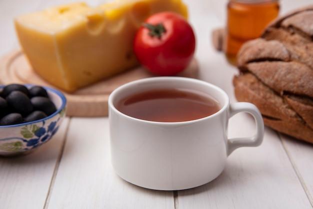 スタンドにトマトオリーブチーズと白い背景の上の黒いパンのパンとお茶の正面図 無料写真
