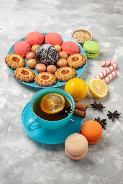 Tazza di tè di vista frontale con i biscotti e le torte francesi dei macarons sui biscotti della caramella della torta dolce del biscotto dello zucchero di superficie bianca Foto Gratuite