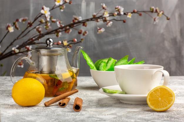 Vista frontale tazza di tè con limoni e cannella sulla superficie bianco-chiaro Foto Gratuite