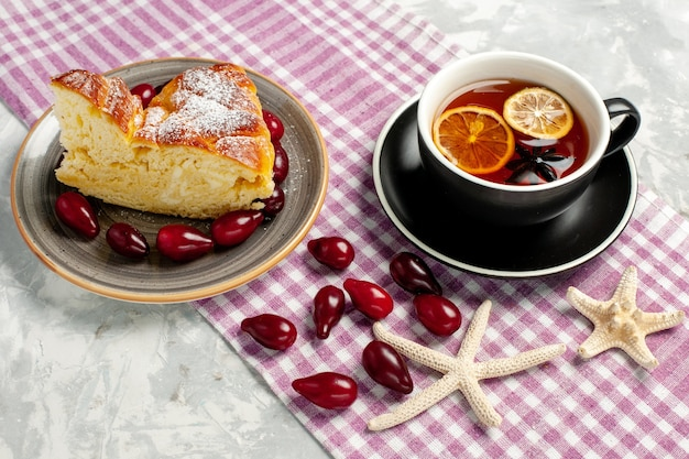 Tazza di tè vista frontale con fetta di torta squisita su superficie bianca Foto Gratuite