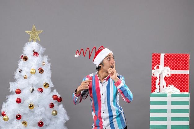 白いクリスマスツリーの近くに立っている何かを観察する正面の好奇心旺盛な男 無料写真