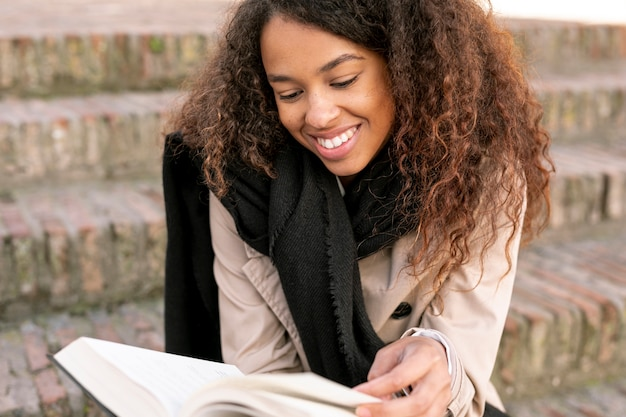 Front view curly woman reading outdoors Free Photo