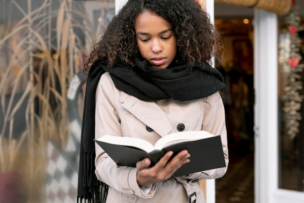 Front view curly woman reading outside Free Photo
