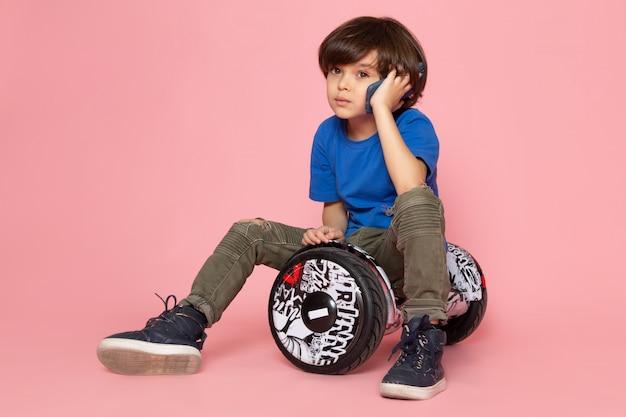 Un ragazzo carino vista frontale in maglietta blu e pantaloni color kaki parlando al telefono in sella segway sul pavimento rosa Foto Gratuite