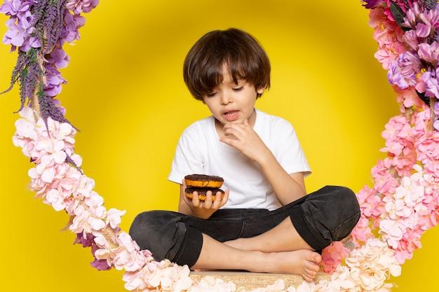Un bambino sveglio di vista frontale che mangia le ciambelle al cioccolato in maglietta bianca sul pavimento giallo Foto Gratuite