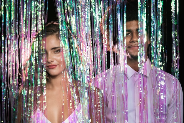 Front view cute couple standing in a curtain of sparkles Free Photo