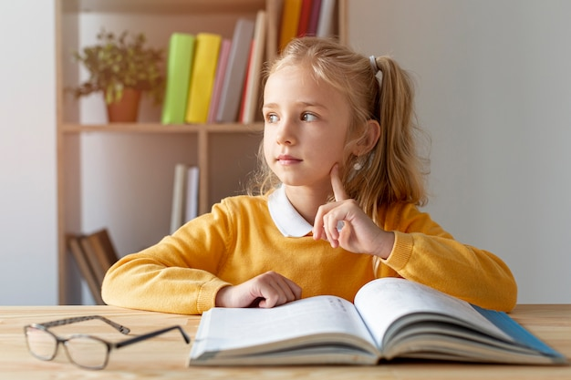 Front view cute girl reading Free Photo
