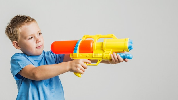 Front view cute kid with water gun Free Photo