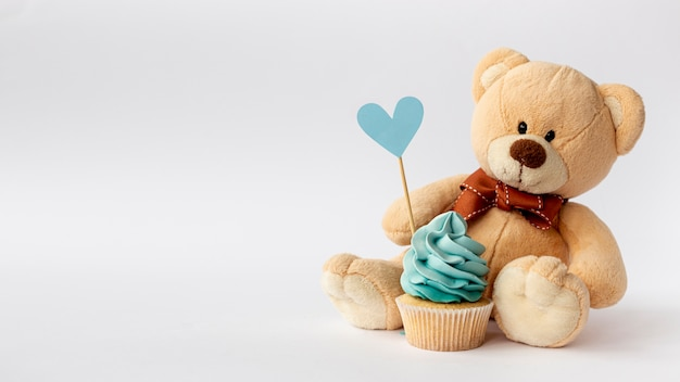 Front view of cute little baby boy cupcake and teddybear Free Photo
