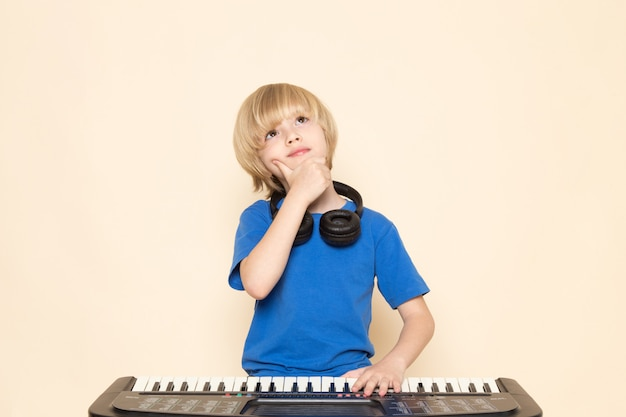 A front view cute little boy in blue t-shirt with black headphones playing little cute piano thinking pose Free Photo