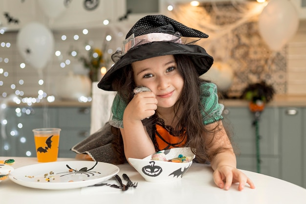 Front view of cute little girl with witch costume Free Photo