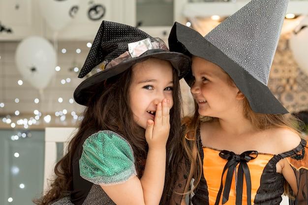 Vista frontale di bambine carine con costume da strega Foto Gratuite