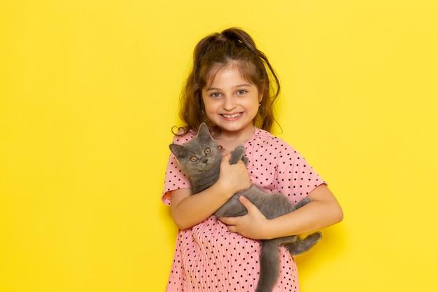 Un ragazzino sveglio di vista frontale in vestito rosa che tiene gattino grigio e sorridente Foto Gratuite