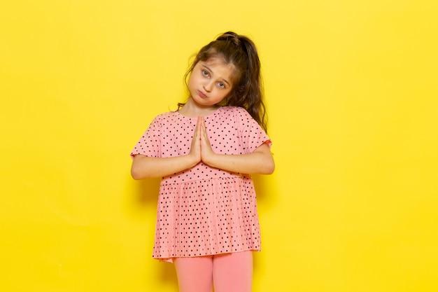 Un ragazzino sveglio di vista frontale in posa rosa del vestito Foto Gratuite