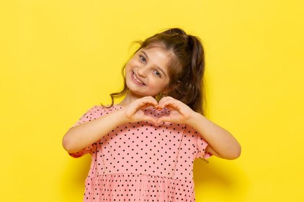 Un ragazzino sveglio di vista frontale in vestito dentellare che sorride e che mostra il segno di amore Foto Gratuite