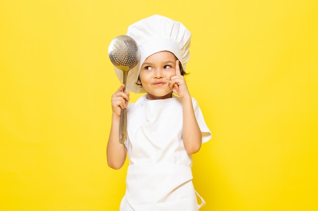 A front view cute little kid in white cook suit and white cook cap holding big spoon on the yellow wall child cook kitchen food Free Photo