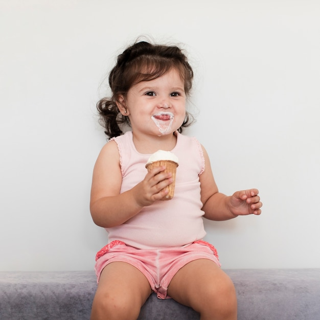 Front view cute young girl eating ice cream Free Photo