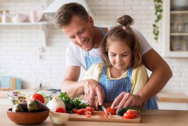 Вид спереди папа приготовления пищи с дочерью Premium Фотографии