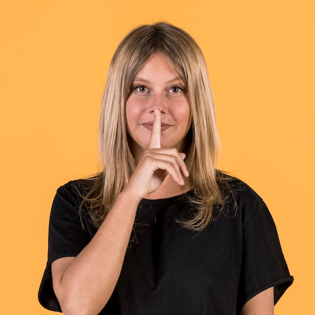 Front view of deaf woman with silent gesture in front of yellow background Free Photo