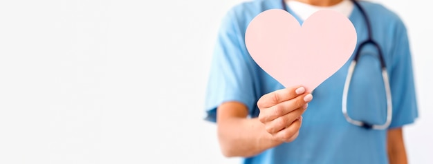 Front view of defocused female doctor holding paper heart Premium Photo