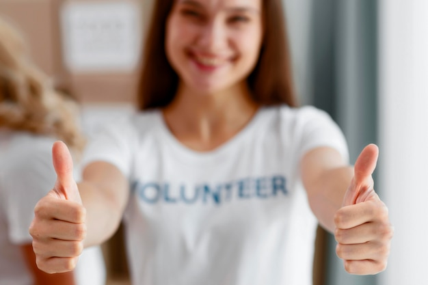 Front view of defocused female volunteer giving thumbs up Free Photo