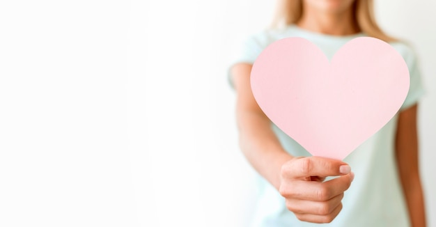 Front view of defocused woman holding heart shape with copy space Free Photo