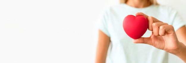 Vista frontale della donna defocused che tiene a forma di cuore Foto Gratuite