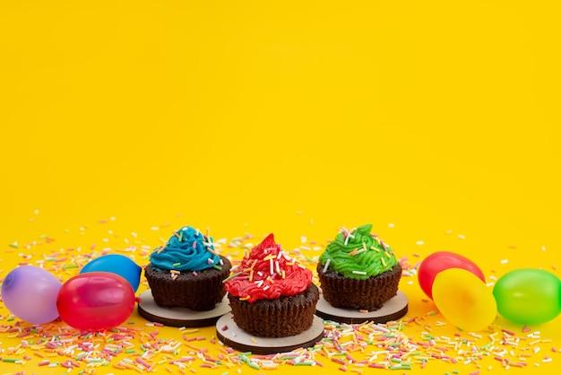 Una vista frontale deliziosi brownies a base di cioccolato insieme a caramelle e palline di colore giallo, caramelle torta biscotto Foto Gratuite