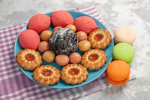 Vista frontale deliziose torte con biscotti e macarons sul muro bianco torta biscotto dolce zucchero torta biscotto Foto Gratuite