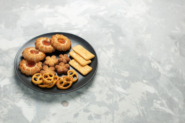 Front view delicious cookies with crackers and crisps inside plate on light white desk Free Photo