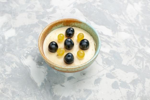 正面図白い表面の小さな鍋の中に果物が上にあるおいしいクリーミーなデザート 無料写真