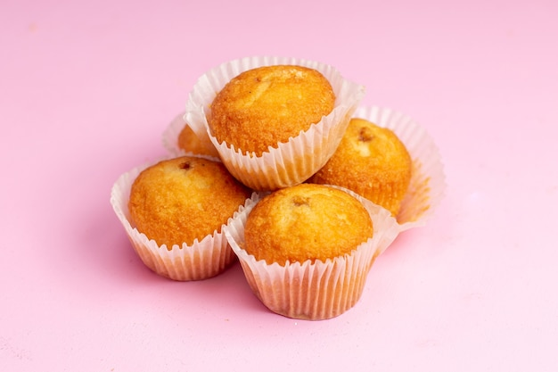正面のピンクの背景にフルーツが入ったおいしい小さなケーキケーキビスケットクッキー甘い砂糖茶 無料写真