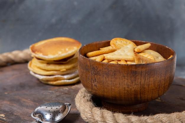 La vista frontale del muffin delizioso rotondo si è formata con le patatine fritte sulla superficie di legno Foto Gratuite