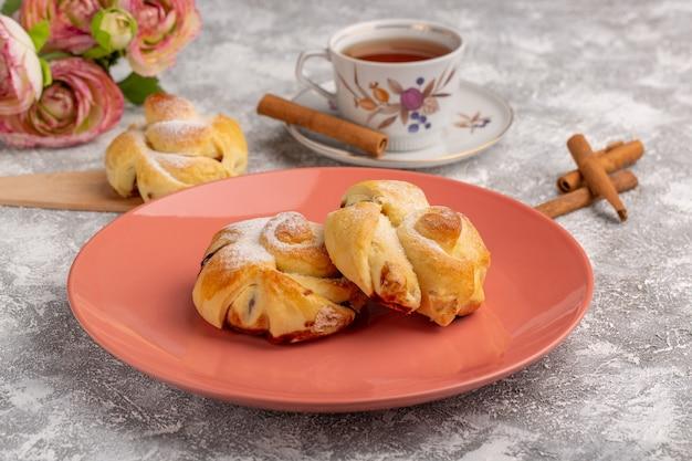 Вид спереди вкусная выпечка с начинкой внутри тарелки вместе с чаем и корицей на белом столе, фруктовый торт, выпечка, печенье Бесплатные Фотографии