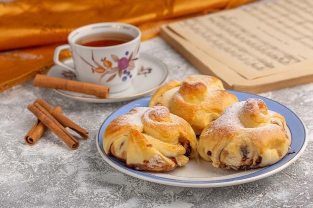正面の白いテーブルにお茶とシナモンと一緒にプレートの内側に充填されたおいしいペストリー、甘い砂糖のケーキでペストリーフルーツを焼く 無料写真