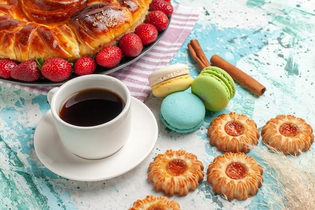Vista frontale deliziosa torta con fragole macarons e tazza di tè sulla superficie blu torta biscotto dolce caramella torta biscotto Foto Gratuite