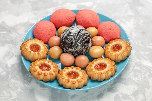 正面図白い表面にクッキーとチョコレートケーキが付いたおいしいピンクのケーキビスケットシュガーケーキ甘いパイティー 無料写真