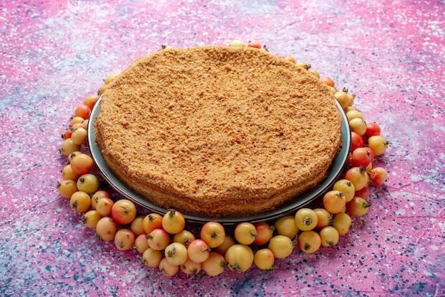 Вид спереди восхитительный круглый торт внутри тарелки с черешнями на ярко-розовом столе, пирог, бисквит, сладкая выпечка, сахар Бесплатные Фотографии