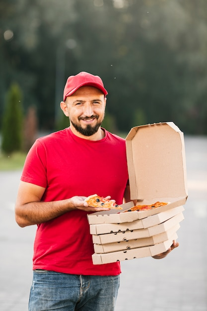 Front view delivery guy holding a pizza slice Free Photo