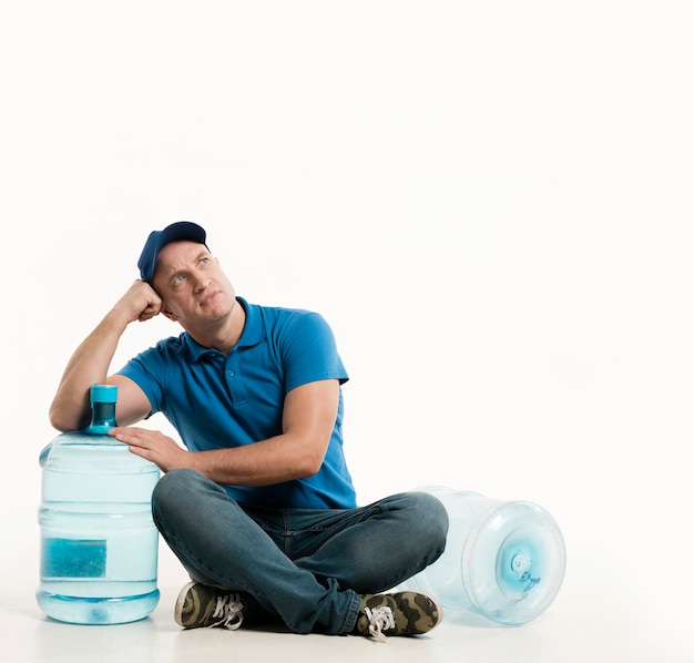 Front view of delivery man posing with water bottle Free Photo