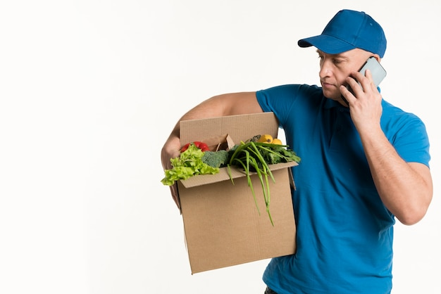 Front view of delivery man with smartphone and grocery box Free Photo