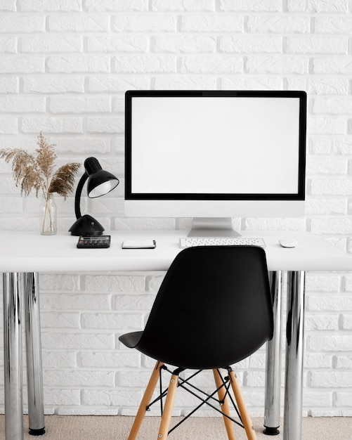 Front view of desk with computer and chair Free Photo