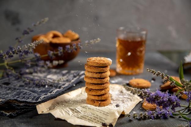 Uno scrittorio di vista frontale con i biscotti e con lo zucchero dolce del biscotto del tè del biscotto del tè sul tavolo grigio Foto Gratuite