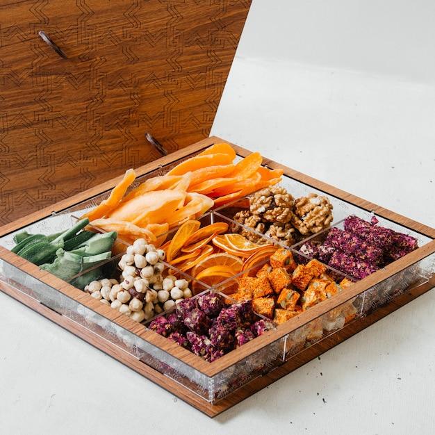 Una scrivania vista frontale con caramelle marmellate di frutta secca e dolci sulla composizione di colore pasticceria dolce scrivania in legno Foto Gratuite
